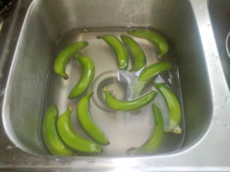 Green bananas in water ready for peeling